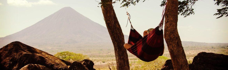 Hängematte mit einem Mensch zwischen zwei Bäumen mit Ausblick auf Gebirge
