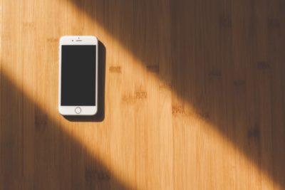 Ausgeschaltetes Handy liegt auf einem Holzhintergrund und wird angestrahlt