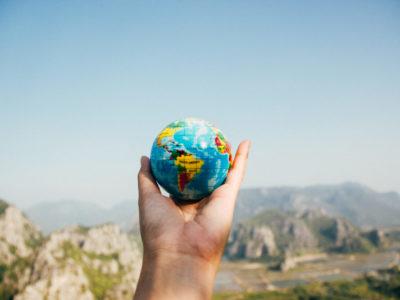 Im Vordergrund hält eine Hand einen Globus in er Hand. Im Hintergrund ist eine Berglandschaft zu sehen
