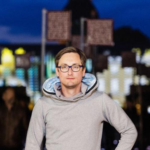 Fabian Krüger am Platz der Grundrechte in Karlsruhe mit grauem Get Lazy Hoodie