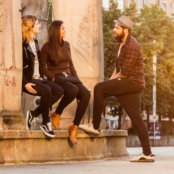 2 weibliche Models sitzen auf Brunnenrand, ein männliches Model steht daneben, alle tragen die kuschelig warmen Get Lazy urban Jogginghosen