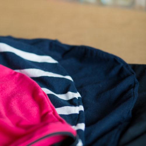 ein pinkes, ein blau-weiß gestreiftes, ein dunkelblaues und ein schwarzes Inlay liegen in einem Halbkreis auf braunem Untergrund