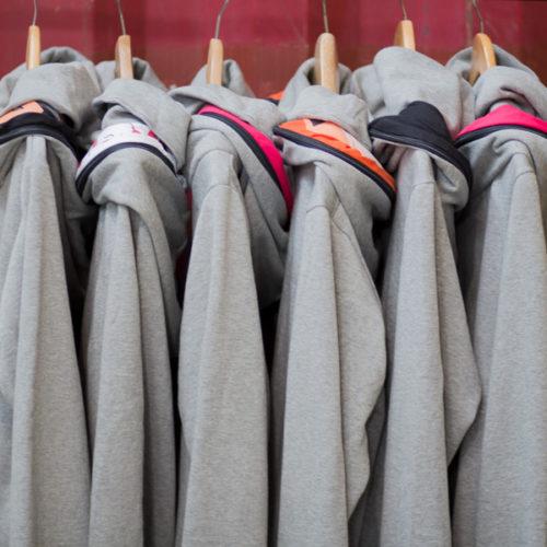 mehrere graue kuschelige Get Lazy Hoodies hängen nebeneinander an einer Kleiderstange