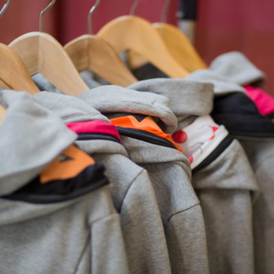 mehrere kuschelige grau melierte Get Lazy Hoodies hängen nebeneinander an einer Kleiderstange