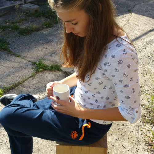 weibliches Model trägt blaue kuschelige Casual Pants und hat eine Get Lazy Tasse auf dem Schoß