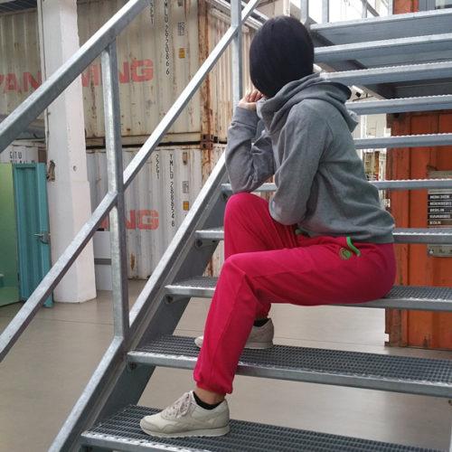 weibliches Model sitzt auf einer Treppe und trägt die pinke bequeme Get Lazy casual Jogginghose