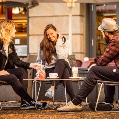 drei Models sitzen zusammen vor einem Café und tragen die gemütliche Get Lazy urban Jogginghose