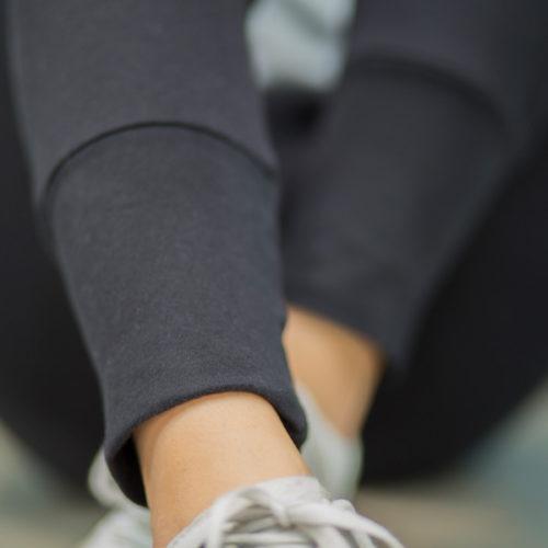 weibliches Model trägt schwarze Get Lazy urban Jogginghose, der Fokus liegt auf dem extra langen Beinbund der Hose