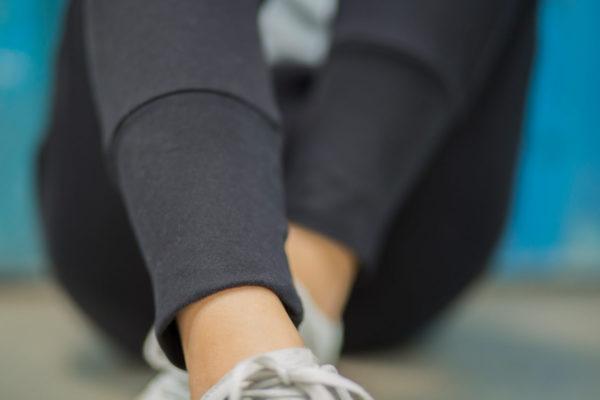 weibliches Model sitzt mit verschränkten Beinen auf dem Boden, der Bund der schwarzen Get Lazy Pants urban ist fokussiert